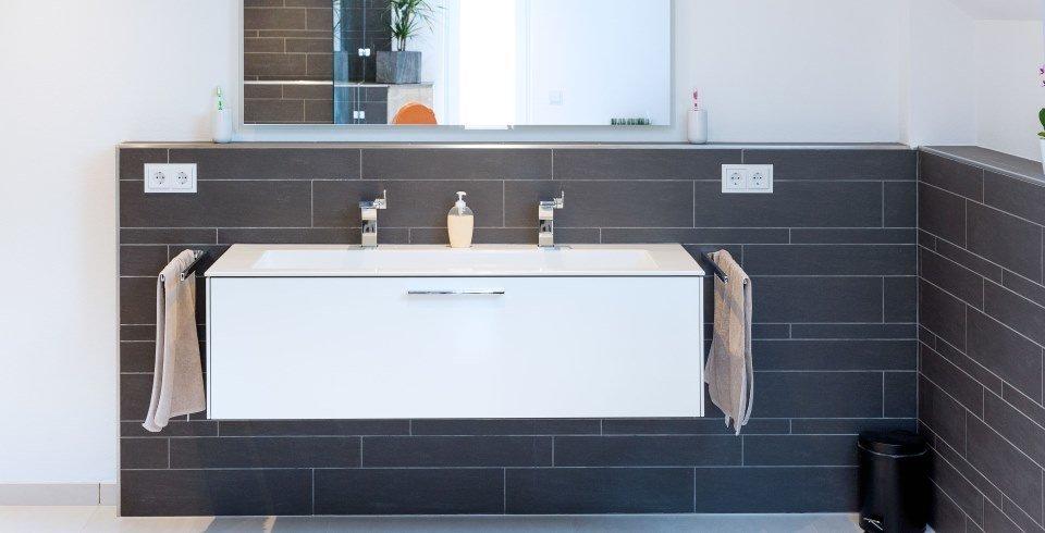Badwand mit schwarzen Fliesen