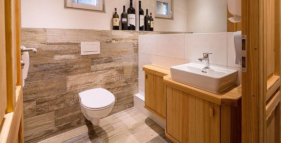 Verflieste Toilette mit Holzoptikfliesen im Weinkeller bei Valentinos Weinkarrussell